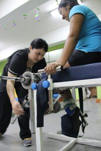 Kinesióloga con paciente pediátrica en el gimnasio reequipado